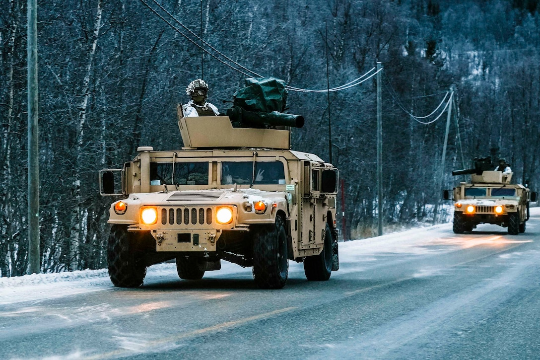 Two military vehicles drive on a snowy road.