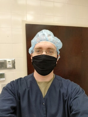 Man in scrubs with mask.
