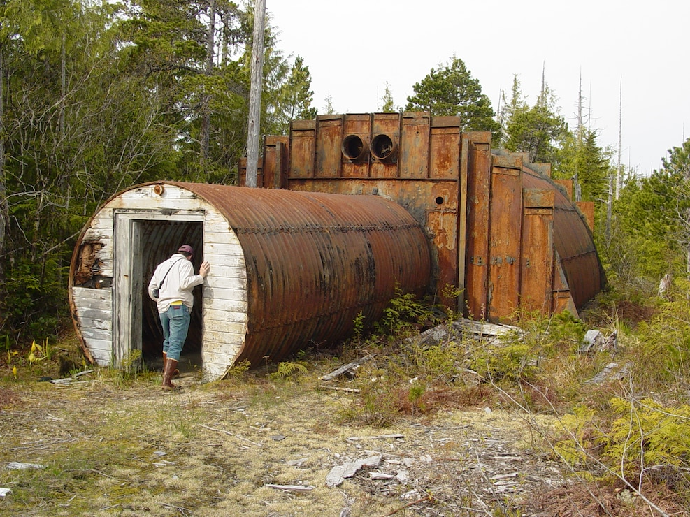 An individual peers into an abandoned military structure on Annette Island. Starting in 1940, the military and other federal agencies used the island for various purposes, leaving structures and debris behind as the land changed hands.