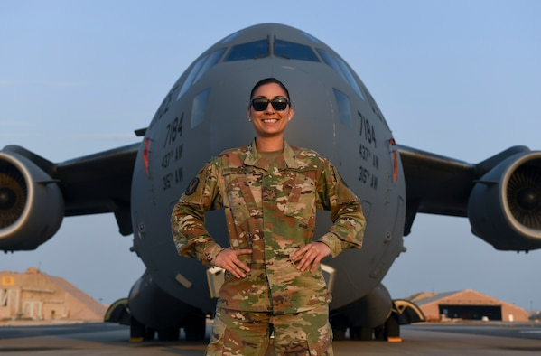 U.S. Air Force Staff Sgt. Cinnamon Kava, 5th Expeditionary Air Mobility Squadron combat oriented support operations supply specialist, poses in front of a C-17 Globemaster III at Ali Al Salem Air Base, Kuwait, Nov. 19, 2020.