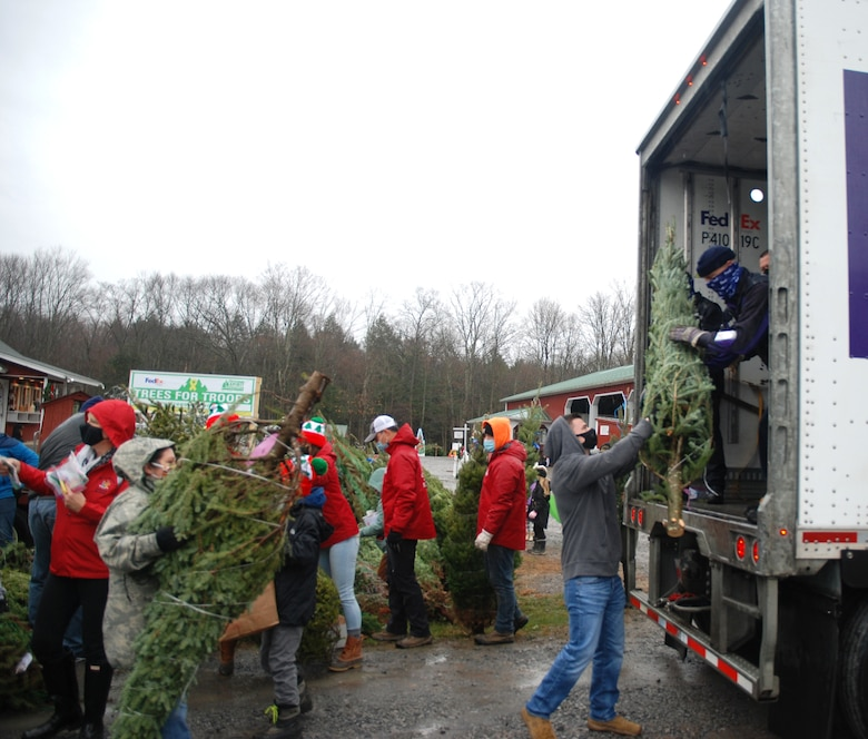 Volunteers pass a tree up to FedEx driver Don Pelletier during the Trees for Troops loadout on Nov. 30, 2020, at Ellms Tree Farm in Ballston Spa, N.Y. More than 20 volunteers from the New York Army and Air National Guard joined with Capital District area veterans to help load about 125 Christmas trees being donated and sent to military bases around the country to support troops and military families this holiday season.