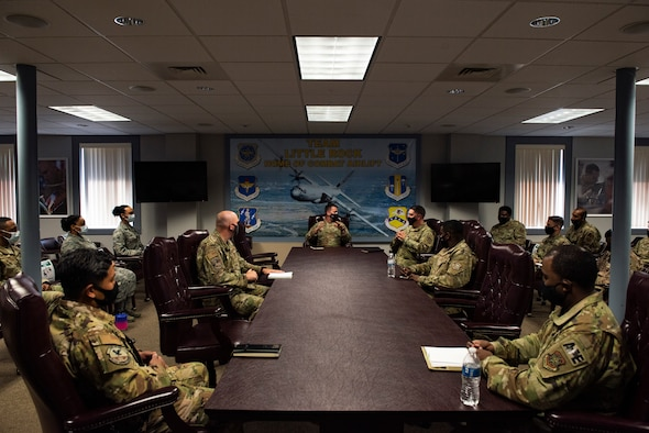 Men and women in conference room sitting around a table.