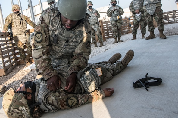 an airman helps secure a bandage around the chest of another airman