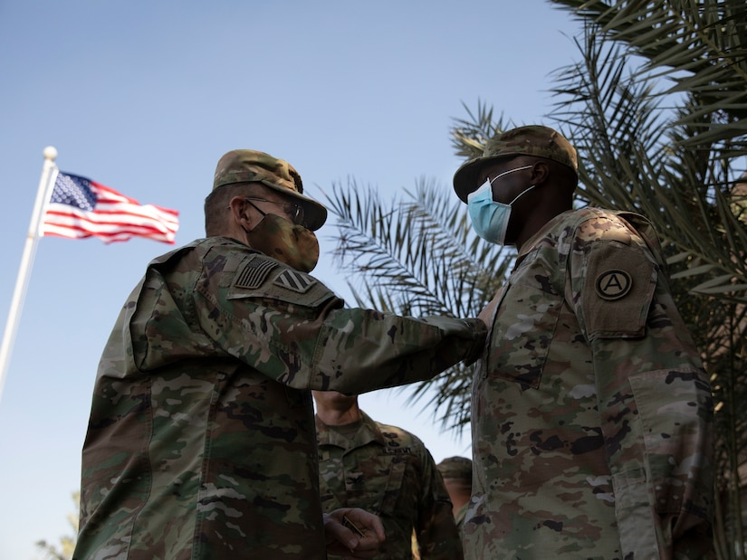 U.S. Army Lt. Gen. Terry Ferrell, commanding general at U.S. Army Central, shares a heartfelt moment with U.S. Army Col. James O. Oyekan, command surgeon, Area Support Group - Kuwait, during a coin ceremony held on Camp Arifjan, Kuwait, November 18, 2020. Ferrell presented Oyekan with the commander's Coin of Excellence for his distinguished leadership providing life-saving force health protection guidance throughout the COVID -19 public health emergency. (U.S. Army Reserve photo by Sgt. Khylee Woodford)