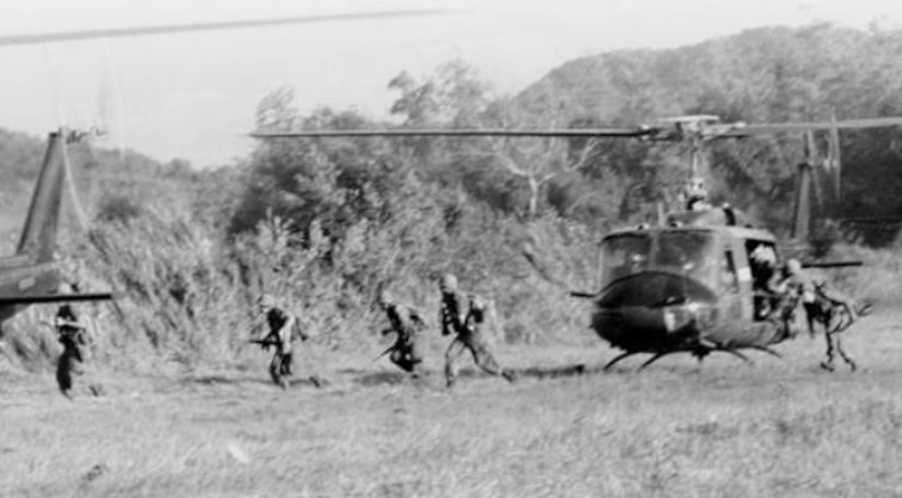Several soldiers run from a helicopter landing in a field.