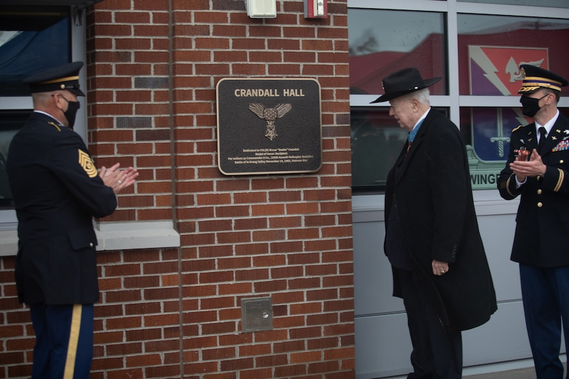 An man looks at a plaque on a building as two soldiers standing near him applaud.