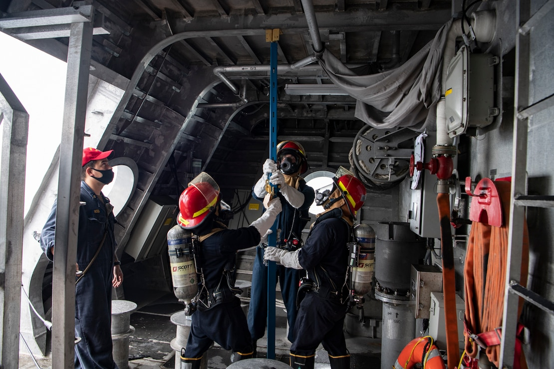 Sailors aboard Independence-variant littoral combat ship USS Gabrielle Giffords (LCS 10) practice using metal shoring during damage control drills, November 28, 2020.