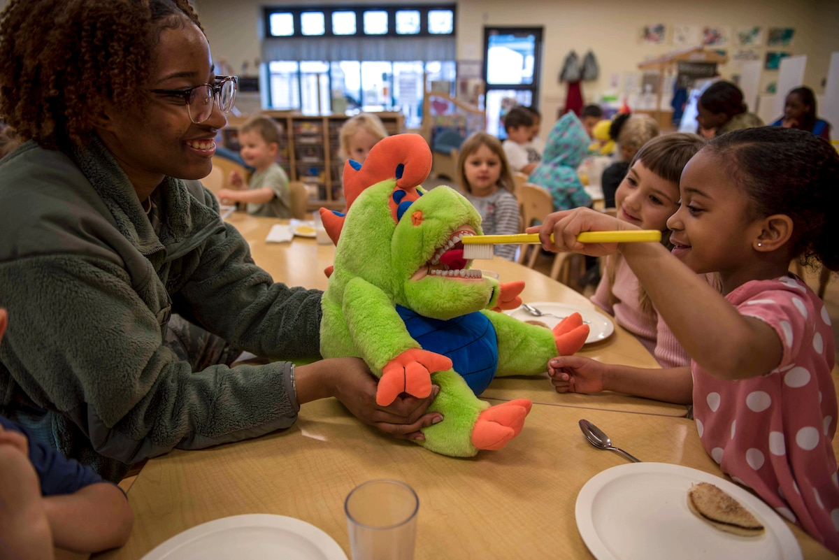 A smiling child brushes a stuffed animal's teeth as an airman and other children watch and smile.