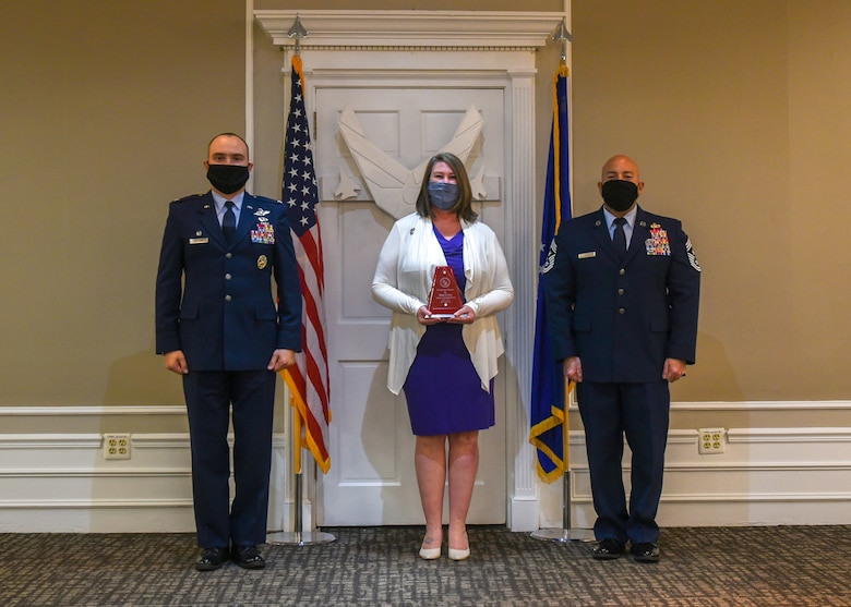A photo of two military members and a civilian with an award.