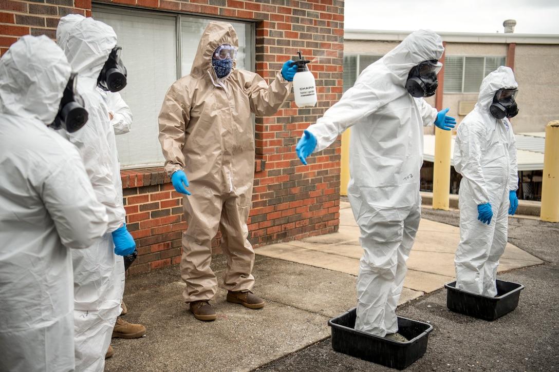 A civilian in protective gear sprays a service member in protective gear standing in bins outside a building.
