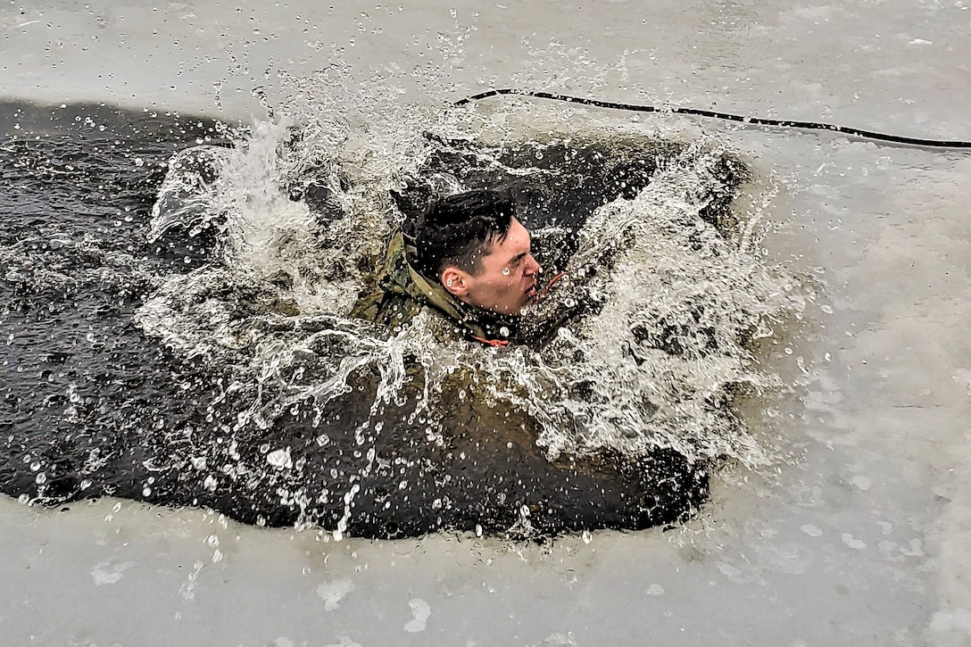 A student makes a splash while plunging into cold water.