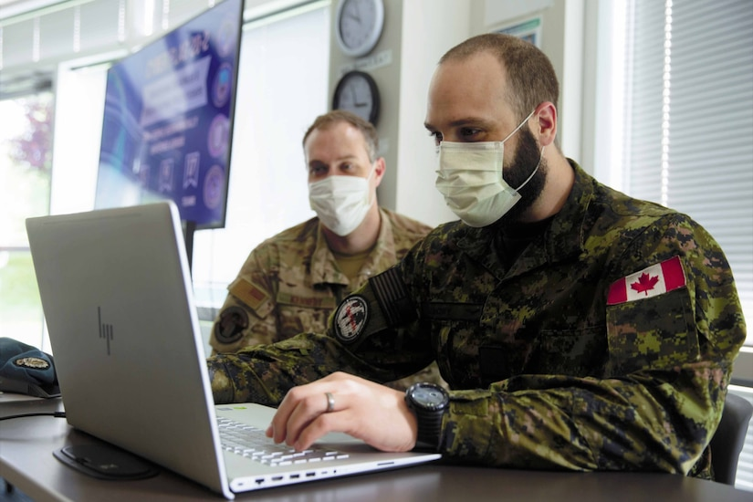 Two men in combat uniforms collaborate over a laptop.