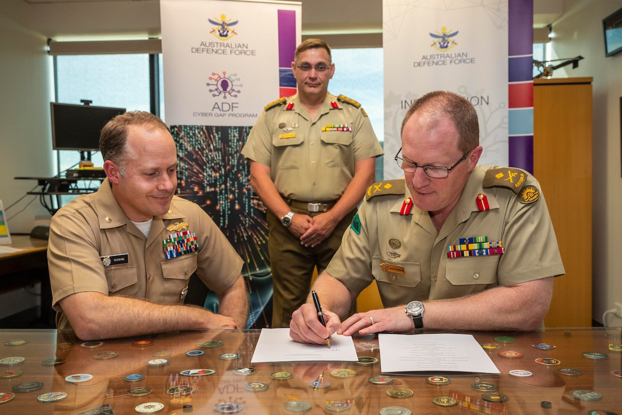 Two men in military uniforms watch a third man sign a document.