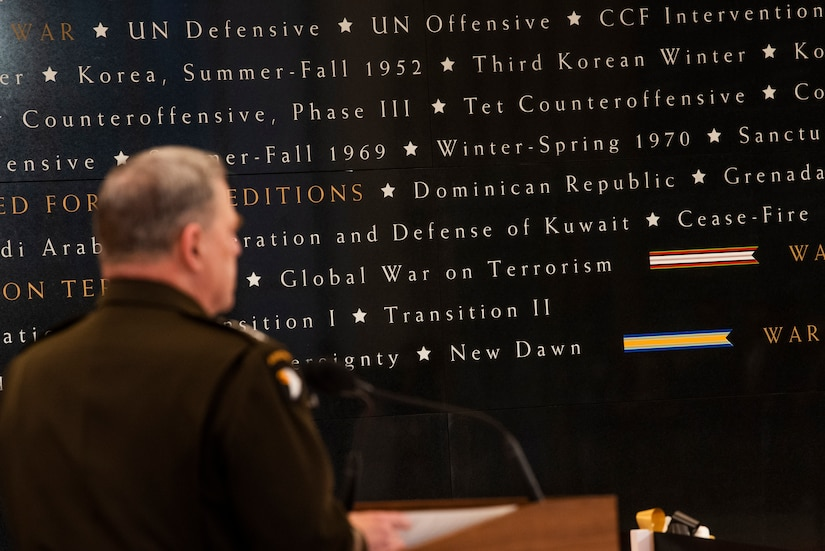 A man is seen from behind as he stands behind a lectern; he faces large words written on a wall.