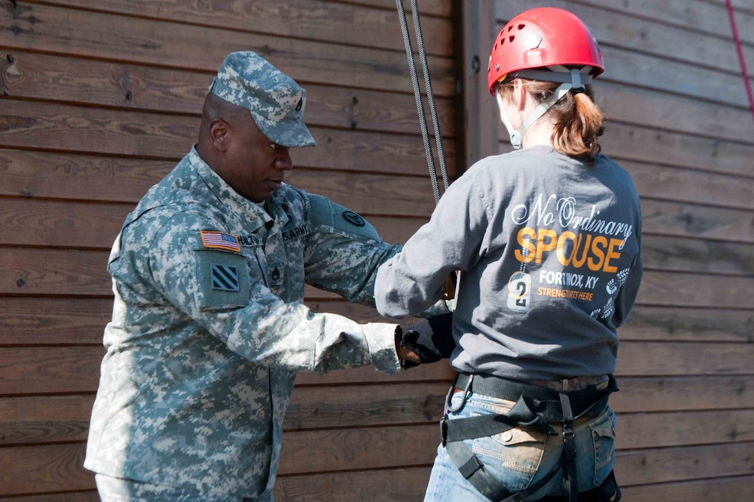 A man in a military uniform handles the cables attached to a woman who is in civilian clothing.