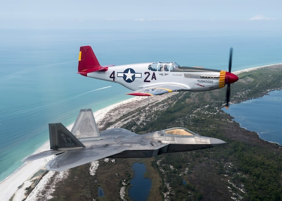 A U.S. Air Force F-22 Raptor aircraft assigned to Tyndall Air Force Base flies in formation with a World War II-era P-51 Mustang, April 22, 2017 over Panama City Beach, Fla. The aircraft flew in support of the opening ceremony of the Gulf Coast Salute Airshow at Tyndall. (U.S. Air Force photo by Staff Sgt. Jason Couillard)