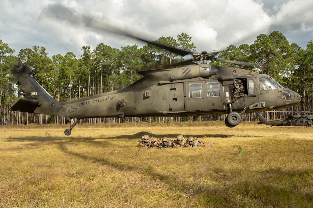 """U.S. Marines provide security after exiting a U.S. Army UH-60M Black Hawk during exercise """"Dogs of War"""" on Fort Stewart, Georgia, Nov. 4."""