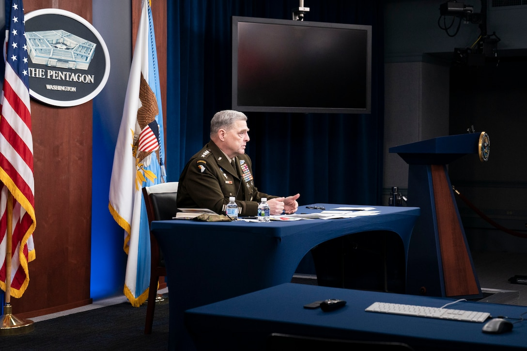 An Army general sits at a table with a Pentagon sign hanging behind him.