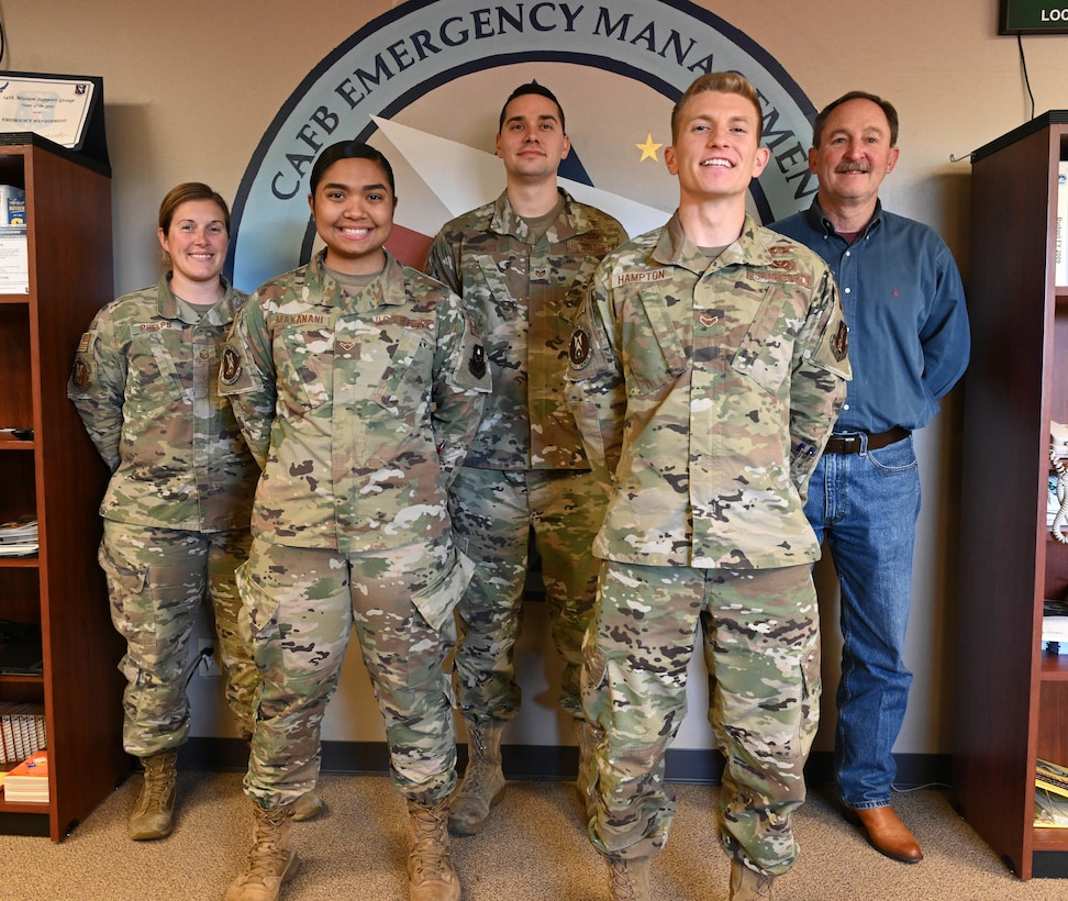 The 14th Civil Engineer Squadron Readiness and Emergency Management flight stands in front of their logo Nov. 24, 2020, on Columbus Air Force Base, Miss. The R&EM flight won the Major Command level Col. Frederick J. Reimer Award which honors the lifetime accomplishments of the man considered to be the founder of Disaster Preparedness and a pioneer of the Air Force's current Readiness Program. (U.S. Air Force photo by Senior Airman Jake Jacobsen)