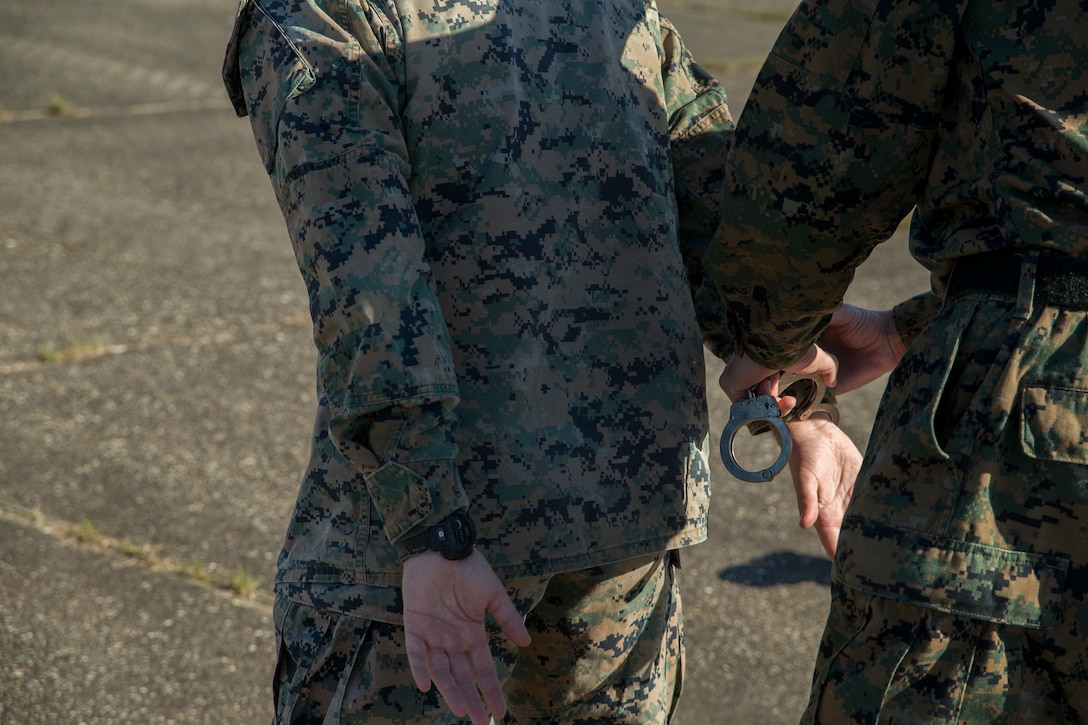 U.S. Marine Corps Cpl. Elliot Holcomb, a military police officer with Headquarters and Headquarters Squadron (H&HS), places Cpl. Riley Callantine, a military working dog handler with H&HS, in handcuffs during an active shooter training exercise at Marine Corps Outlying Field (MCOLF) Atlantic, North Carolina, Nov. 17, 2020. Cherry Point's Provost Marshal's Office regularly familiarize it selves with arresting procedures in order to conduct them in a real life situation without hesitation. MCAS Cherry Point facilitates a wide spectrum of training grounds, to include special air space and coastal areas, allowing for a multitude of training conditions useful for supporting almost any training scenario. (U.S. Marine Corps photo by Lance Cpl. Jacob Bertram)