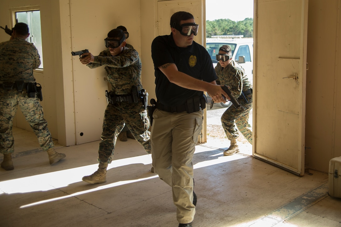 U.S. Marine and civilian police officers with the Marine Corps Air Station (MCAS) Cherry Point's Provost Marshals Office (PMO) clear a room during an active shooter training exercise at Marine Corps Outlying Field (MCOLF) Atlantic, North Carolina, Nov. 17, 2020. This type of training enables Cherry Point's PMO to be ready to respond to a wide variety of threats that may occur on the installation. MCAS Cherry Point facilitates a wide spectrum of training grounds, to include special air space and coastal areas, allowing for a multitude of training conditions useful for supporting almost any training scenario. (U.S. Marine Corps photo by Lance Cpl. Jacob Bertram)