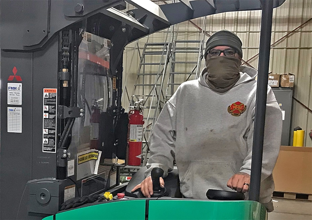 A masked man drives material handling equipment in a warehouse.