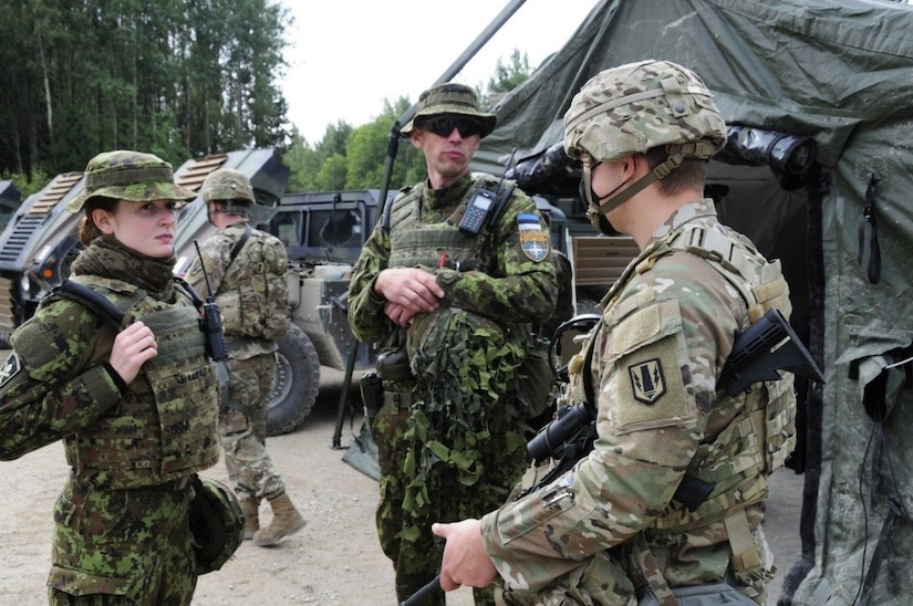 Three soldiers in combat uniforms talk outside a tent.
