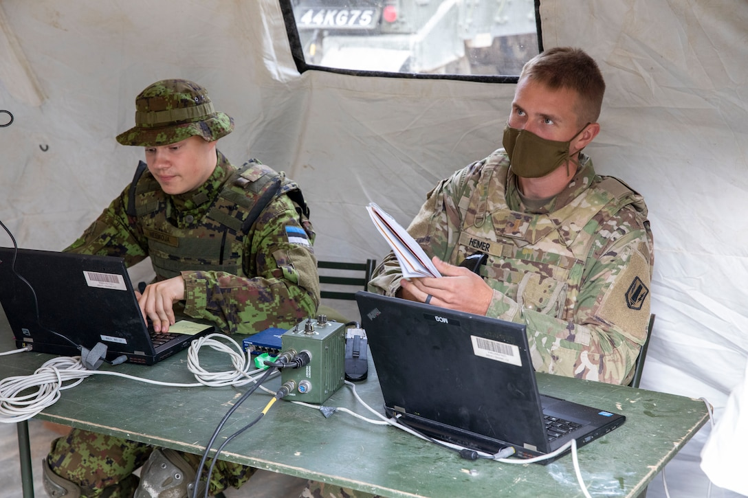Two soldiers in combat uniforms sit behind laptops at a table.