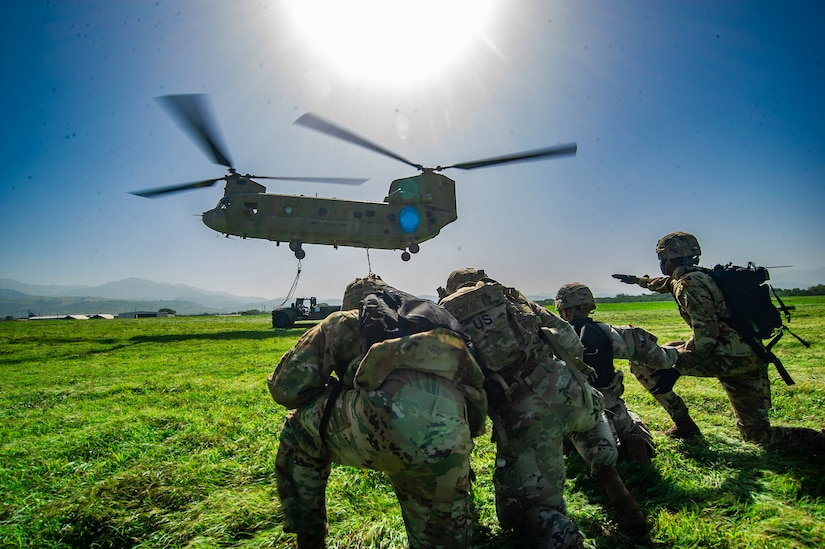 Soldiers wait to attach a sling to a descending helicopter.