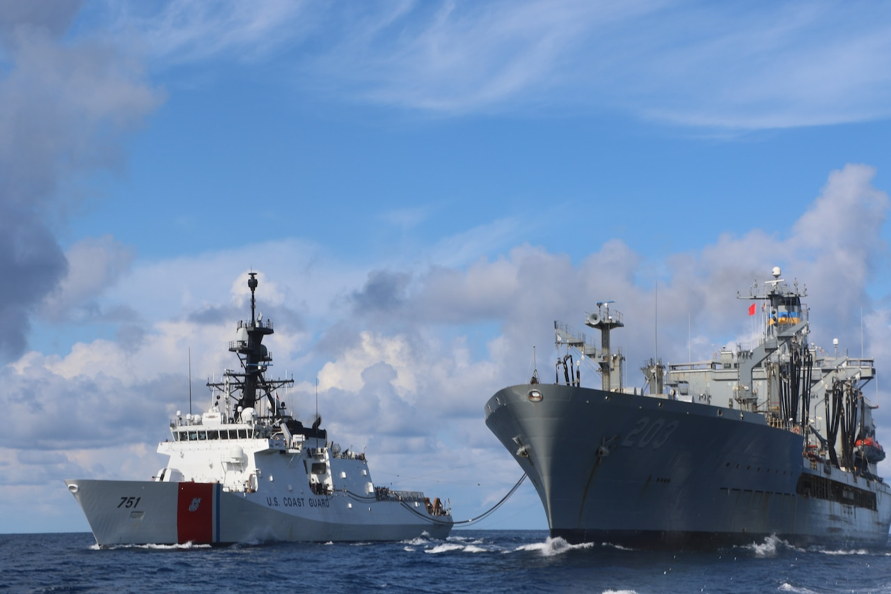 Two ships sit beside one another with a cable stretched between them. U.S. Coast Guard is written on the side of one ship.