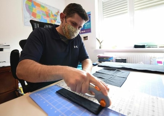OSI 4th Field Investigations Squadron Special Agent Justin Acree cuts fabric for protective masks. SA Acree personally made 1,556 face covers for communities across Germany to help cope with the COVID-19 pandemic. (U.S. Air Force photo by SrA Elizabeth Baker, Ramstein AB/PA)