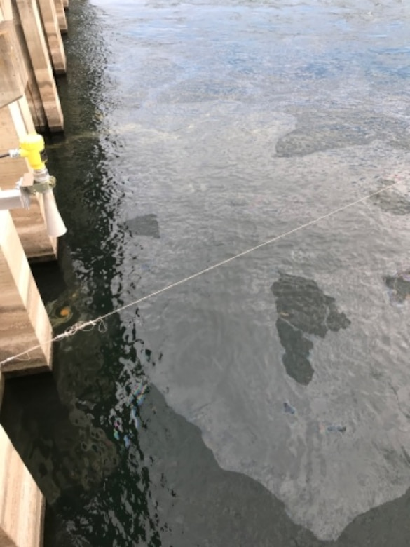 Oil sheen seen in at The Dalles Dam on the Columbia River, Dec. 3, 2020. On Thursday, a thrust hub cooling water pipe broke, spilling up to 200 gallons of oil into the Columbia River at The Dalles Dam. The equipment is part of a fish unit turbine designed to provide attraction water for migrating fish.  The U.S. Army Corps of Engineers, Portland District is dedicated to rapid spill responses and is in the process of containing as much oil as possible. The turbine is now isolated from the river.