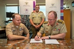 (Left to right) U.S. Navy Programs Manager, Lt. Cmdr. Mike Tomsik and Australian Army Colonel Hamish Ashman watch as Head Information Warfare Australian Army Major General Marcus Thompson signs a cyber training agreement between Australia and the United States at Russell Offices on 3 November 2020.  The United States and Australian Cyber Training Capabilities Project Arrangement will help Defence build its cyber capability through information-sharing and training initiatives.