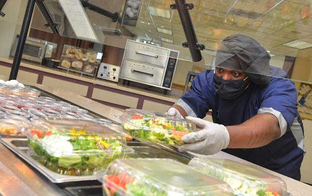 Image of Navy Culinary Specialist 3rd Class Keith Johnson prepping food.