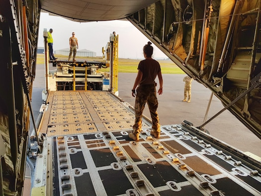 A woman stands on C-130 ramp while loading equipment