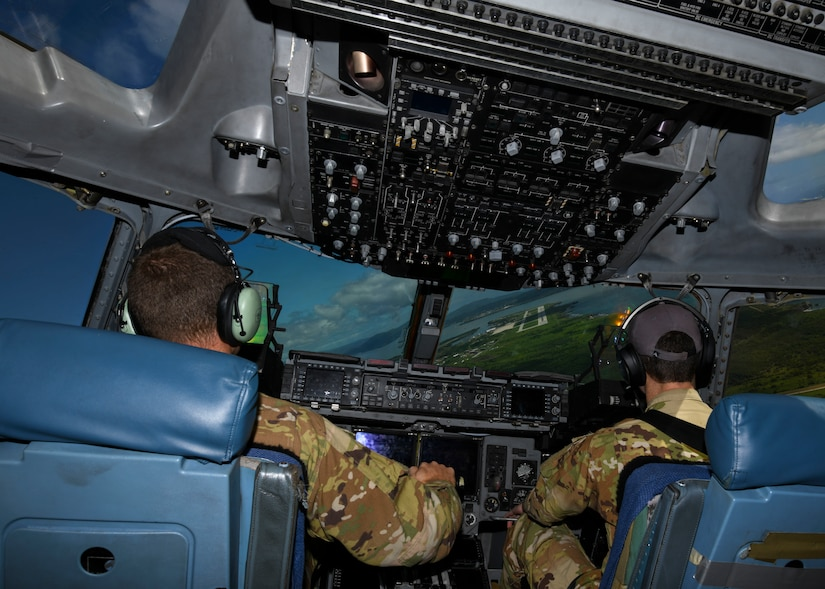 Capt. Chris Brown, a C-17 Globemaster III pilot, and Capt. Spencer Dewey, a C-17 Globemaster III aircraft commander, who are both assigned to the 15th Airlift Squadron at Joint Base Charleston, S.C., prepare to land at Naval Station Guantanamo Bay (NSGB), Cuba, Nov. 12, 2020. The 15th AS flew an off-station trainer to NSGB to deliver two Halverson loaders and bring two Halverson loaders back to Charleston. The aircrew also conducted airfield and low-level training at Guantanamo Bay, Cuba, the Florida Keys, Lakeland Linder International Airport and Patrick Air Force Base. Two Airmen, assigned to the 628th Logistics Readiness Squadron at Joint Base Charleston, repaired two loaders before they were loaded onto the jet.