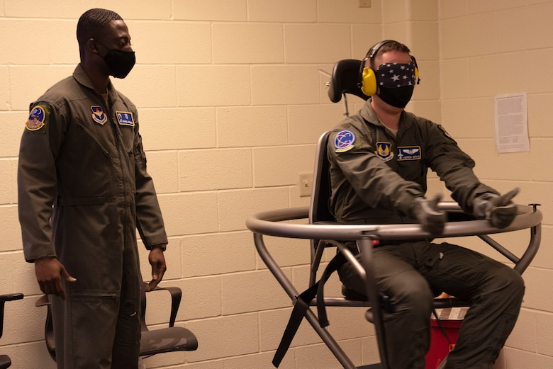 Airman 1st Class Gaddiel Acquaah, 47th Operations Support Squadron aerospace physiology technician, spins 2nd. Lt. Andrew Servis, 586th Flight Test Squadron, a flight test engineer, in a Barany Chair on Nov. 23, 2020, Laughlin Air Force Base, Texas. The Barany Chair spins a person carefully at first and progressively becomes more violent, and is designed to train pilots to avoid throwing up when their inner ear becomes disoriented while flying. (U.S. Air Force photo by Airman 1st Class David Phaff)