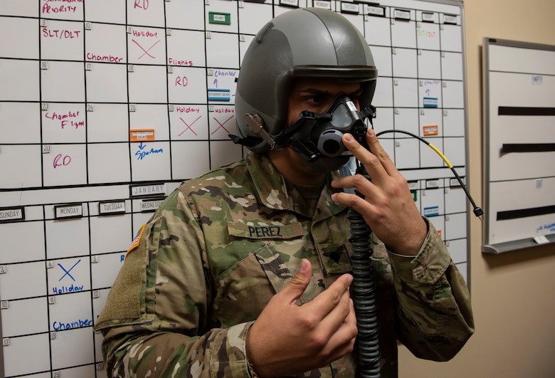 Spc. Santiago Perez, 204th Military Intelligence Battalion cryptologic linguist, gets fitted for a helmet and mask before going to the chamber on Nov. 23, 2020, Laughlin Air Force Base, Texas. This equipment is used to help breathe when in high altitudes. (U.S. Air Force photo by Airman 1st Class David Phaff)