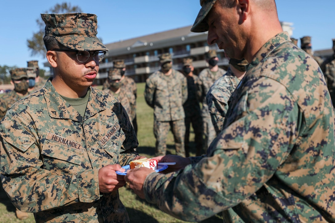 U.S. Marine Corps Col. Paul C. Merida, right, the 22nd Marine Expeditionary Unit commanding officer, passes a piece of cake to the youngest Marine in attendance during a cake cutting ceremony commemorating the 245th Birthday of the United States Marine Corps aboard Camp Lejeune, N.C., Nov. 20, 2020. (U.S. Marine Corps photos by Cpl. Tawanya Norwood)