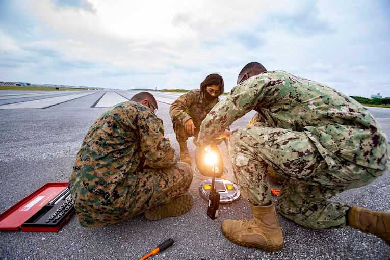 Three Marines repair a light while sitting and kneeling on an airfield.