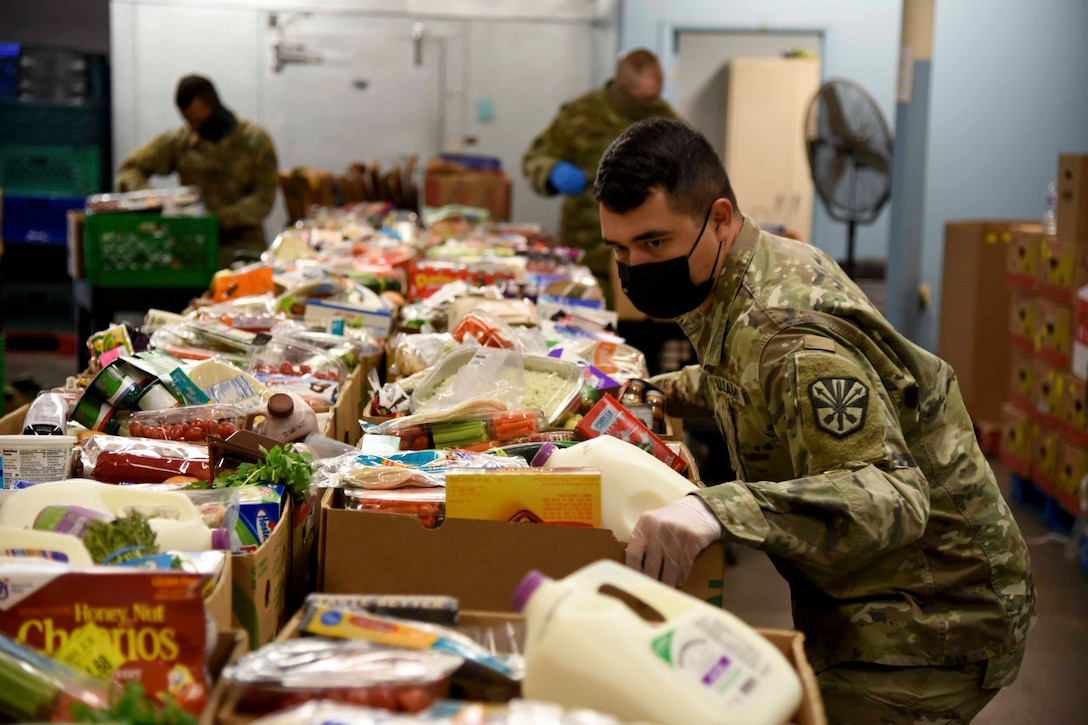 A Guardsman adjusts boxes of groceries.