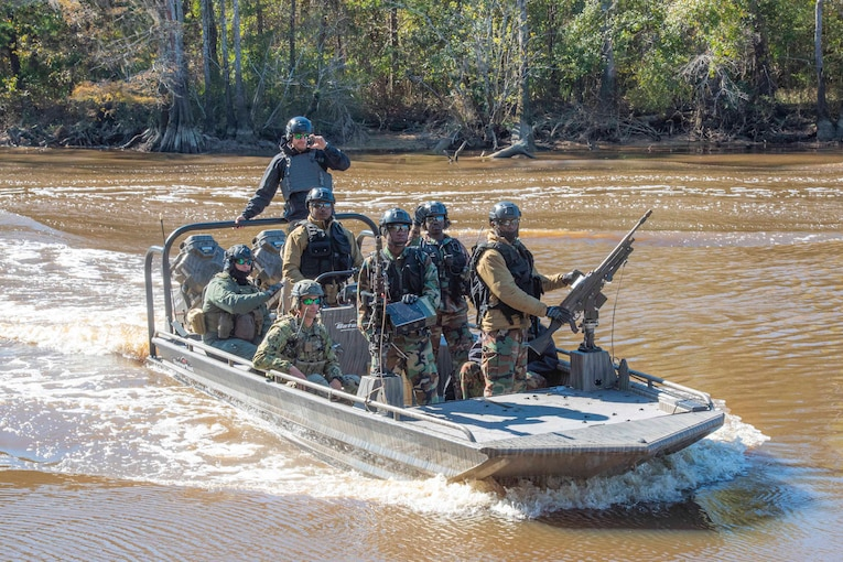 A group of foreign service members ride in a boat through a river; a tree line can be seen behind.