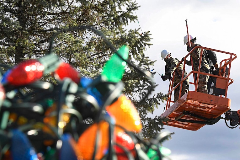Two airmen stand on a forklift putting string lights on a tree.