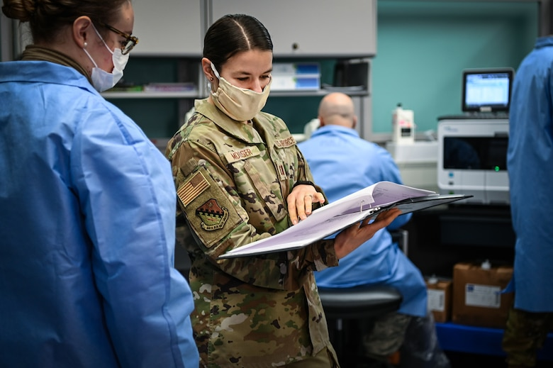 Capt. Jenifer Mouser, 66th Medical Squadron Laboratory officer in charge, center, discusses COVID-19 testing procedures with Airman 1st Class Kaylin Rice, laboratory technician, at the Hanscom Air Force Base, Mass., clinic, Dec. 3. The five-Airman team is responsible for collecting and testing all routine lab work as well as COVID tests taken on the installation. (U.S. Air Force photo by Todd Maki)