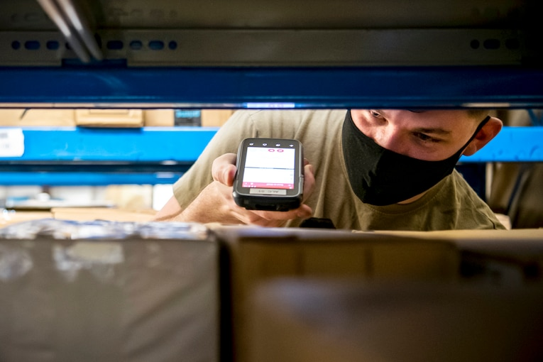 An airman wearing a face mask holds a scanner up to packages on shelves.