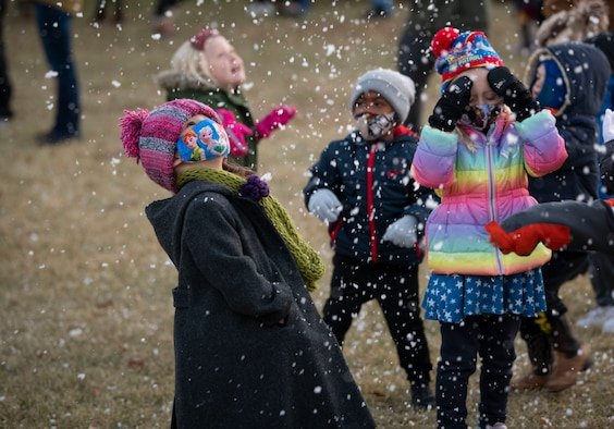 """Children play in """"snow"""" at the annual holiday tree lighting event, Dec. 3, 2020, at Altus Air Force Base, Oklahoma. The snow was made of soapsuds that were blown from a snow machine. (U.S. Air Force photo by Airman 1st Class Amanda Lovelace)"""