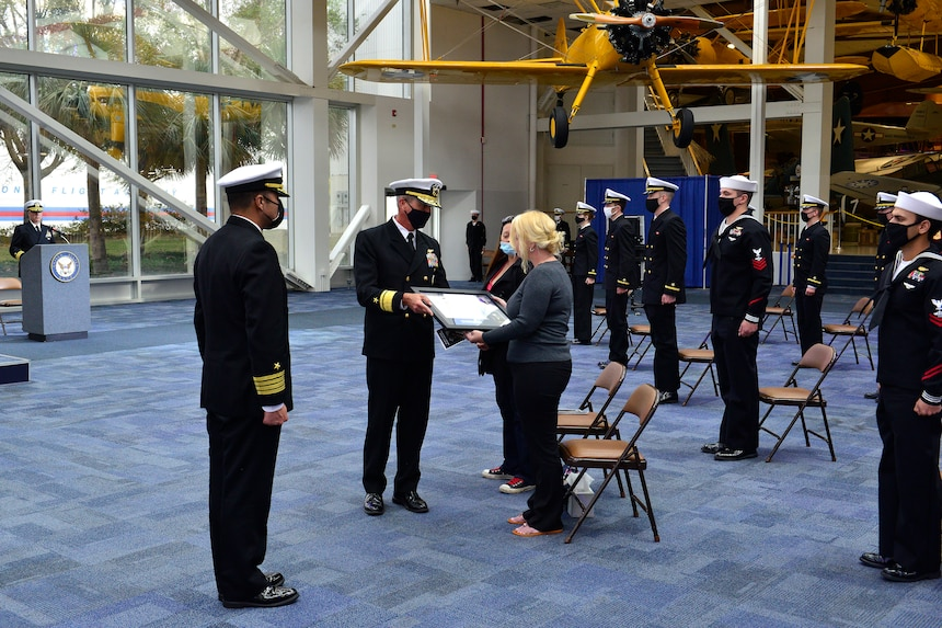 The family of Petty Officer 3rd Class Cameron Walters is presented a Purple Heart Medal posthumously by Rear Adm. Pete Garvin, commander, Naval Education and Training Command.