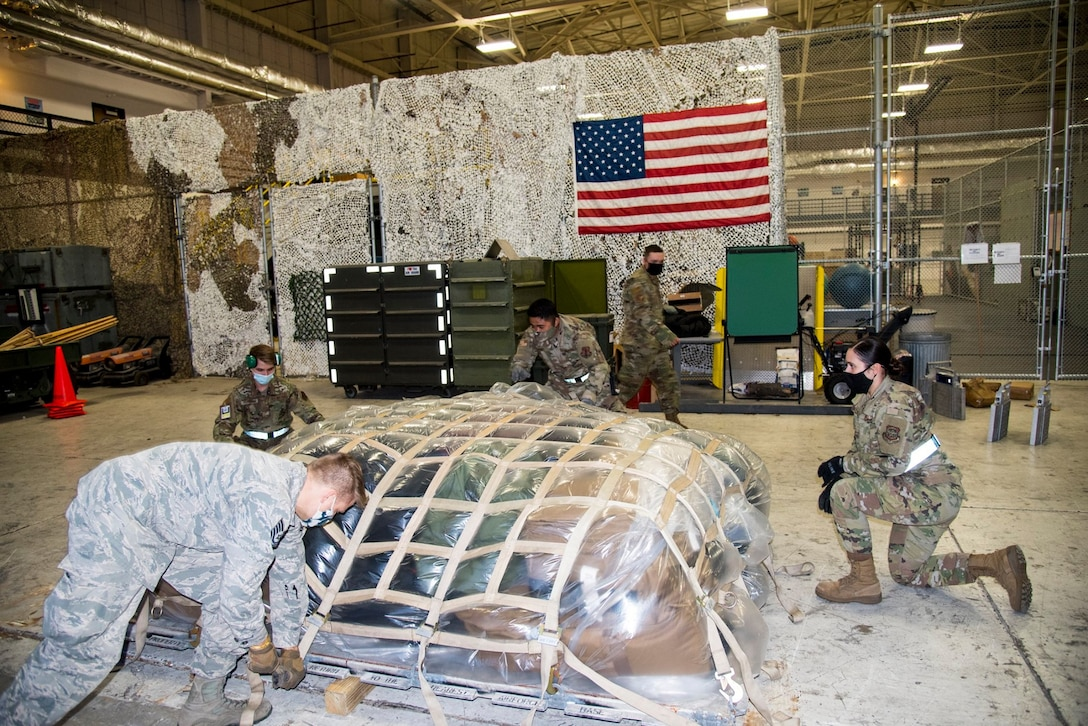 Deployers from the 108th Wing, strap down a pallet in preparation to leave to the U.S. Central Command's area of responsibility, in the 108th Security Forces Squadron's hangar at Joint Base McGuire-Dix-Lakehurst, N.J., Dec. 1, 2020. More than 80 New Jersey Air National Guardsmen departed to provide expeditionary support for Operation Freedom's Sentinel, Operation Inherent Resolve and Operation Spartan Shield until spring 2021. (U.S. Air National Guard photo by Staff Sgt. Kenneth Brown)