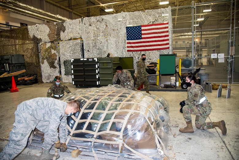 Deployers from the 108th Wing, strap down a pallet in preparation to leave to the U.S. Central Command's area of responsibility, in the 108th Security Forces Squadron's hangar at Joint Base McGuire-Dix-Lakehurst, N.J., Dec. 1, 2020.