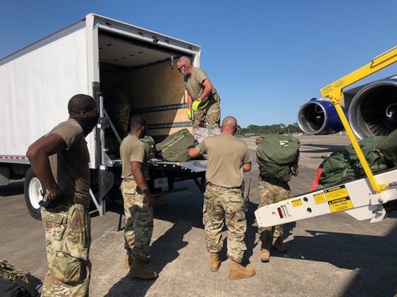 Members of the Air National Guard and the 403rd Wing work together loading bags onto the airplane with the deployers at Camp Gulfport, which is located at the Gulfport Combat Readiness Training Center, where one Restriction of Movement operation was set up in order to prevent the spread of COVID-19. ROMs were put into effect before all deployments start, in order to ensure the safety of service members in the U.S. Central, Africa, and European Commands area of responsibilty. (U.S. Air Force photo by Lt. Col. Shawn Baldy)
